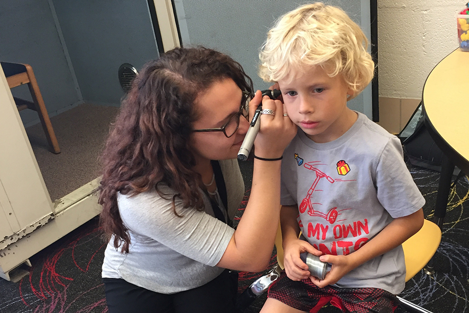 A student looking into a child's ear.
